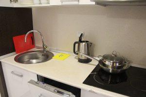 Посуда на кухне, электрический чайник, мойка, плита.